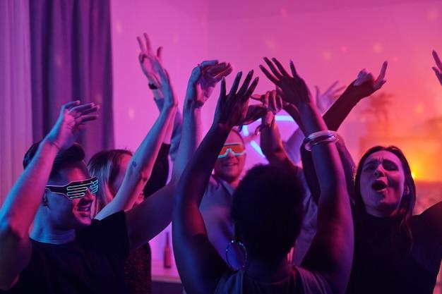 Jonge interculturele glamoureuze vrienden heffen hun armen op terwijl ze samen dansen op een thuisfeest in de woonkamer verlicht met roze verlichting