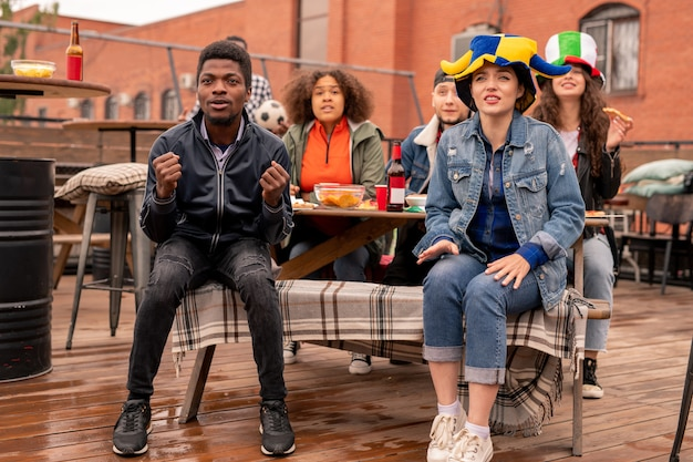 Jonge interculturele paar voetbalfans en hun vrienden zitten op terras, bier met snack hebben en kijken naar wedstrijduitzending