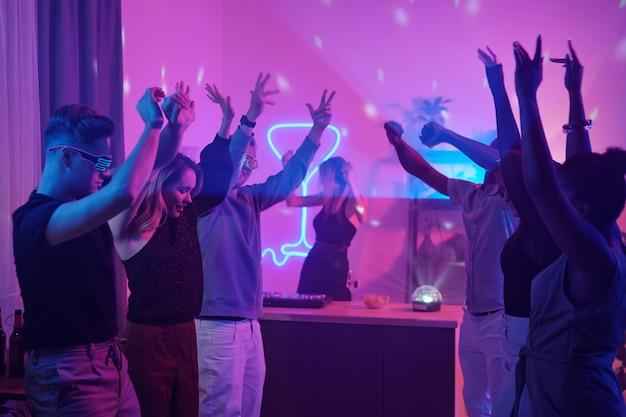 Jonge interculturele vrienden in slimme vrijetijdskleding die hun armen opheffen terwijl ze samen dansen op een thuisfeest in de woonkamer verlicht met roze verlichting