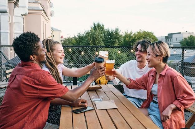 Jonge interculturele vrienden roosteren met drankjes boven houten tafel