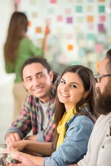 Jonge interieurontwerpers zitten op kantoor en brainstormen