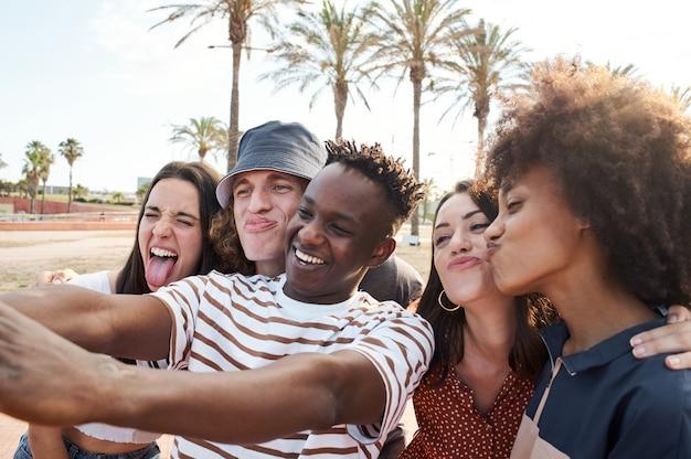 Jonge interraciale vrienden nemen een foto terwijl ze dwaas spelen. groep mensen die samen genieten van hun vrije tijd.