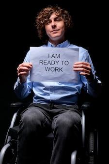 Jonge invalide man geeft niet op ondanks handicap, op zoek naar werk, klaar om te werken als iedereen, geïsoleerd op zwarte muur