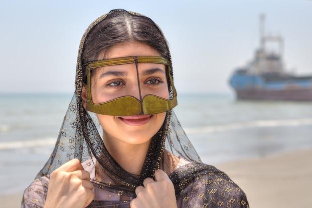 Jonge iraanse vrouw in traditioneel masker van moslimvrouwen in het zuiden van iran, glimlachend, staande op de oever van de perzische golf.
