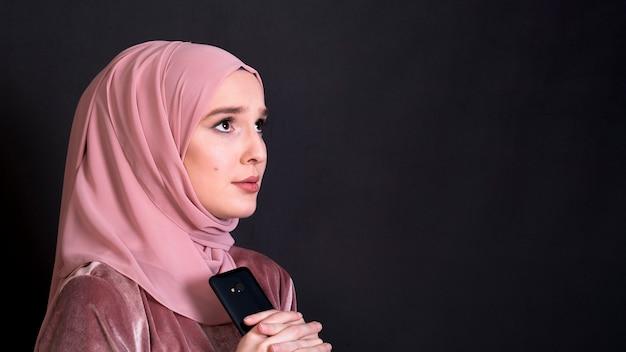 Jonge islamitische enge vrouw die weg over zwarte achtergrond kijkt