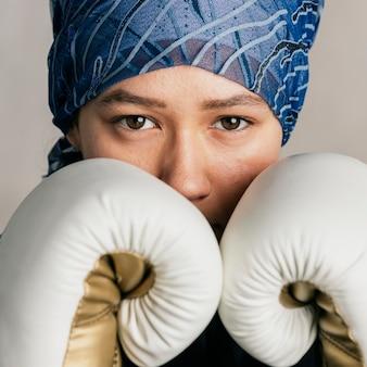 Jonge islamitische vrouw die een bandana draagt tijdens het boksen
