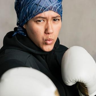 Jonge islamitische vrouw die een sporthijab draagt tijdens het boksen