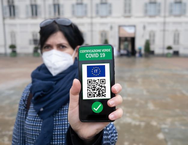 Jonge italiaanse vrouw met smartphone met green pass qr-code bevestigt dat vaccin niet is toegestaan