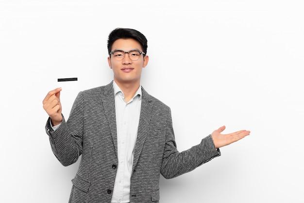 Jonge japanse man die vrolijk glimlacht, zich gelukkig voelt en een concept in exemplaarruimte met handpalm toont. creditcard concept.