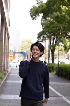 Jonge japanse man in een blauwe trui buitenshuis