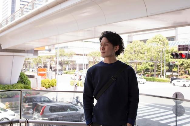 Jonge japanse man in een blauwe trui in de stad