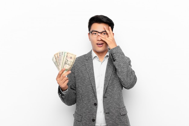 Jonge japanse man kijkt geschokt, bang of doodsbang, kegelvormig gezicht met hand en gluren tussen vingers. geld concept