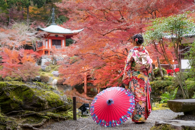 Jonge japanse meisjesreiziger in traditionele kiminokleding die zich in digoji-tempel met rode pagode en rood esdoornblad bevinden in de herfstseizoen in kyoto, japan.