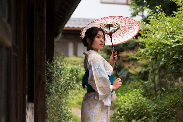 Jonge japanse vrouw die een kimono draagt en een paraplu houdt