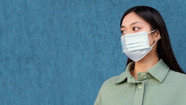 Jonge japanse vrouw die masker draagt
