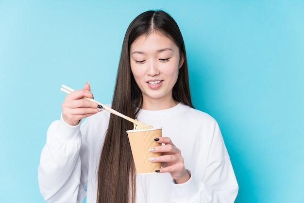 Jonge japanse vrouw die noedels eet