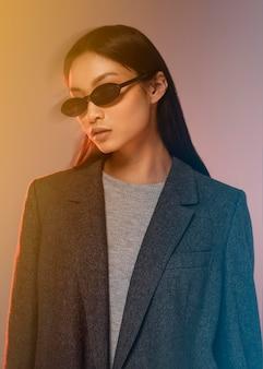 Jonge japanse vrouw met jasje dat zonnebril draagt