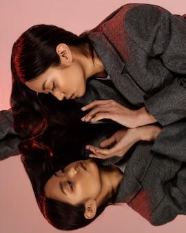 Jonge japanse vrouw met jasje poseren in spiegel