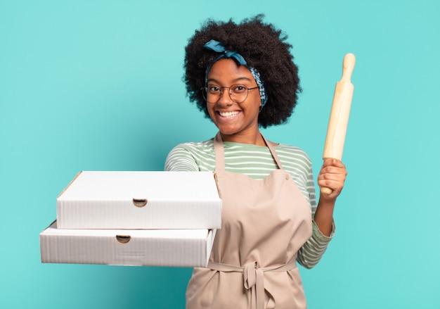 Jonge jonge afro vrouw chef-kok met een deegroller en pizza's