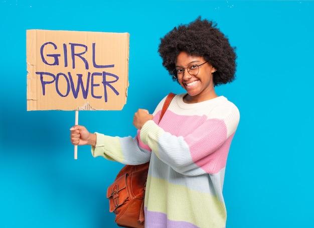 Jonge jonge afrovrouw met de banner van de meisjesmacht