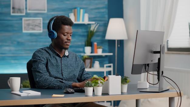 Jonge jonge manager die een koptelefoon gebruikt om naar muziek te luisteren terwijl hij vanuit het thuiskantoor op een computer-pc werkt