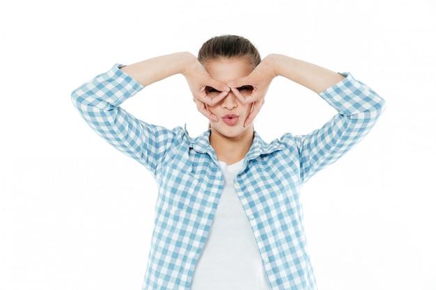 Jonge jonge vrouw die bij camera grimassen trekken die over wit wordt geïsoleerd
