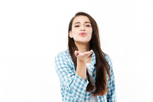 Jonge jonge vrouw die een luchtkus geeft