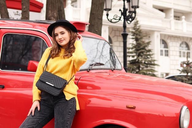Jonge jonge vrouw in zwarte hoed in de buurt van rode auto