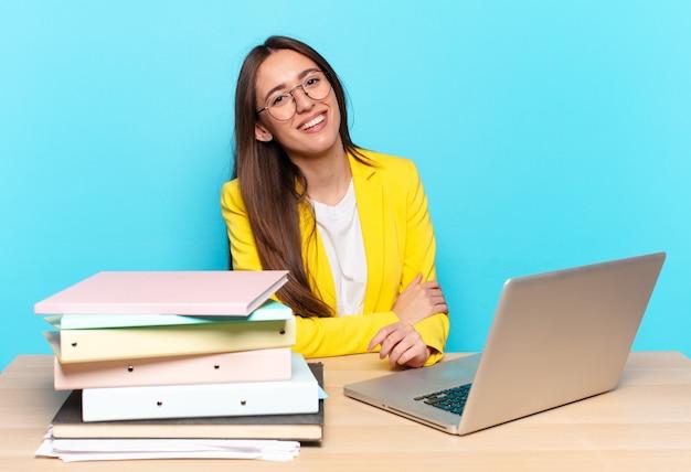 Jonge jonge zakenvrouw die verlegen en opgewekt lacht, met een vriendelijke en positieve maar onzekere houding