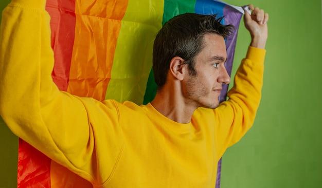 Jonge jongen aan de kant met regenboogvlag op groene achtergrond, lgbti, homo