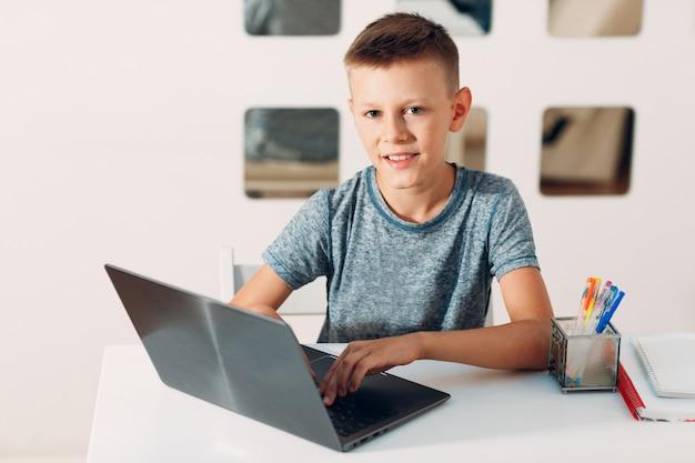 Jonge jongen aan tafel zitten met laptop en de voorbereiding op school thuis