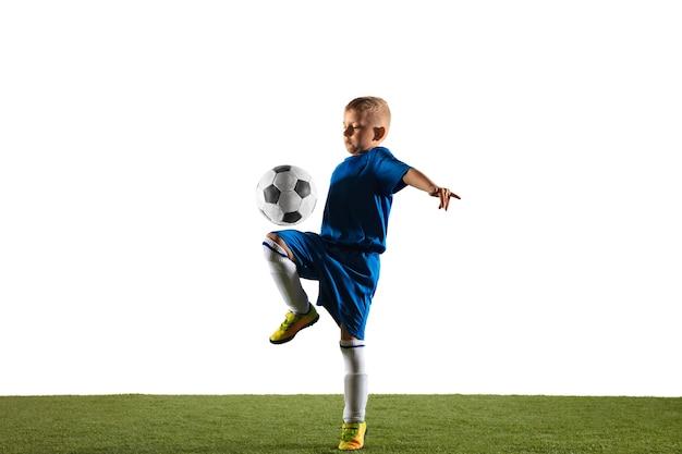 Jonge jongen als een voetbal of voetballer in sportwear die een schijnbeweging of een schop met de bal voor een doel op witte achtergrond maakt.