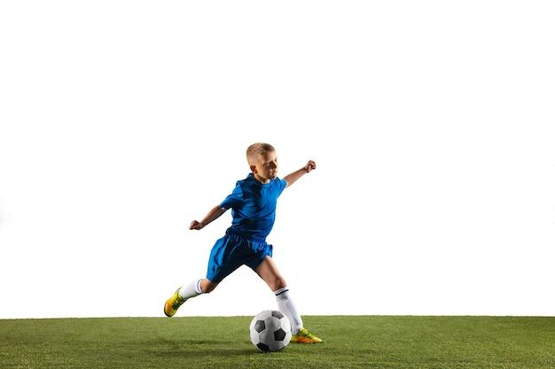 Jonge jongen als voetbal of voetballer in sportkleding die een schijnbeweging of een trap maakt met de bal voor een doel op een witte muur.