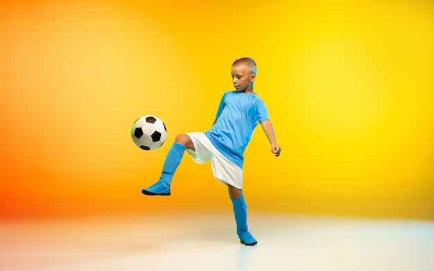 Jonge jongen als voetbal- of voetballer in sportkleding die oefent op geel verloop