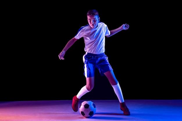 Jonge jongen als voetbal of voetballer op donkere muur
