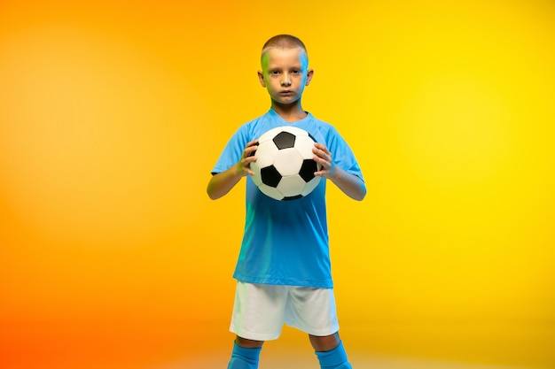 Jonge jongen als voetballer in sportkleding geïsoleerd op gele muur met kleurovergang in neon