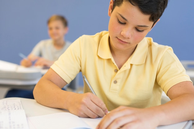 Jonge jongen bij school het schrijven