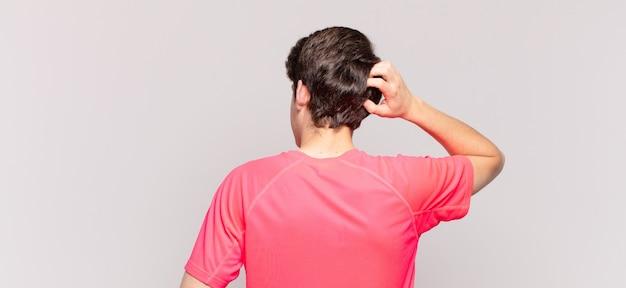 Jonge jongen denkt of twijfelt, krabt aan zijn hoofd, voelt zich verward en verward, achter- of achteraanzicht