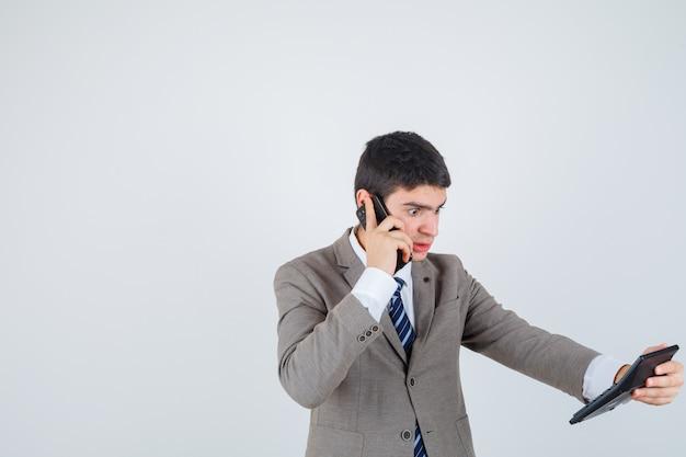 Jonge jongen die aan telefoon spreekt, calculator in formeel kostuum bekijkt en verbaasd kijkt. vooraanzicht.