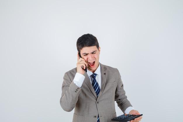 Jonge jongen die aan telefoon spreekt, calculator in formeel kostuum houdt en op zoek gekweld. vooraanzicht.