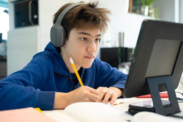 Jonge jongen die computer en mobiel apparaat gebruikt die online studeert. onderwijs en online leren.