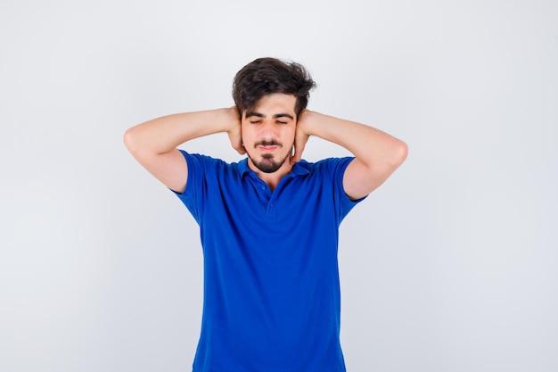 Jonge jongen die de handen op de oren drukt in een blauw t-shirt en er gehaast uitziet. vooraanzicht.