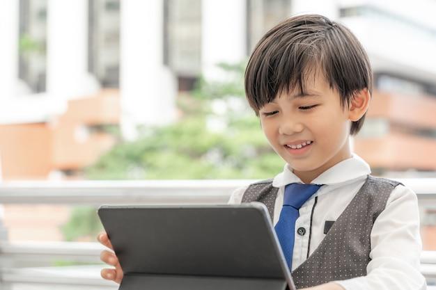 Jonge jongen die de slimme computer van de telefoontablet op stedelijke bedrijfsdistrict, onderwijsconcept met behulp van
