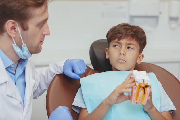 Jonge jongen die de tandarts verdacht bekijkt, voorbereidend op zijn cariës tandheelkundige behandeling bij de kliniek