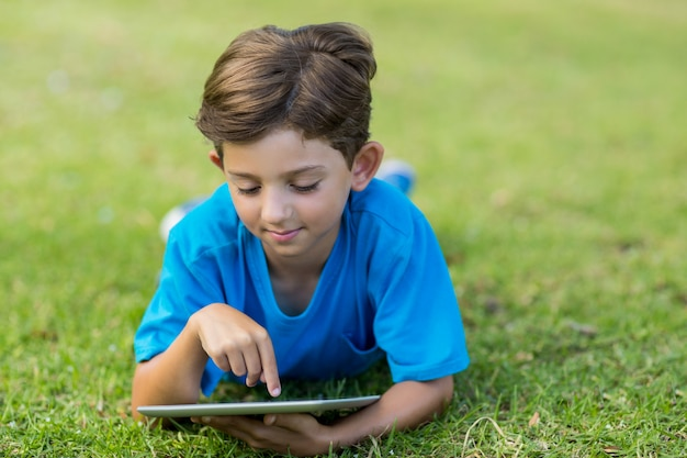 Jonge jongen die digitale tablet in park gebruikt