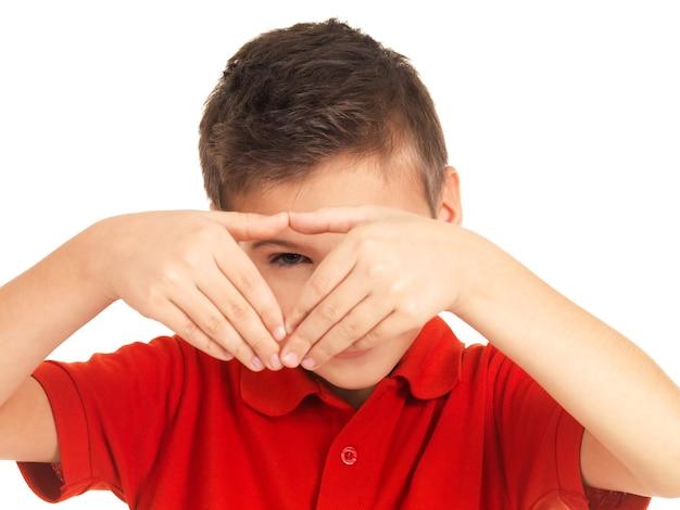 Jonge jongen die door hartvorm kijkt die op wit wordt geïsoleerd