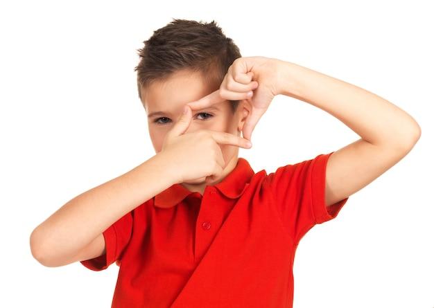 Jonge jongen die door kadervorm kijkt die door handen op wit wordt geïsoleerd