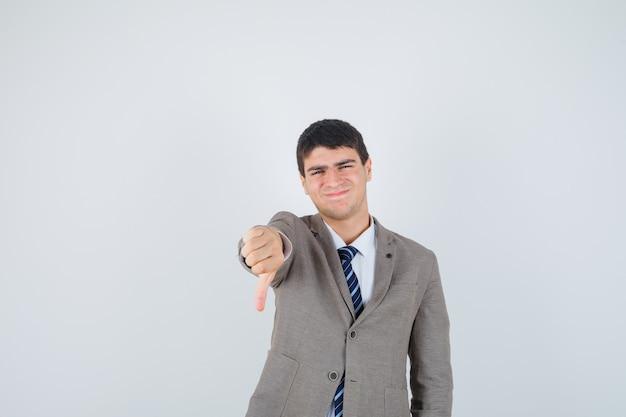 Jonge jongen die duim in formeel kostuum toont en teleurgesteld, vooraanzicht kijkt.