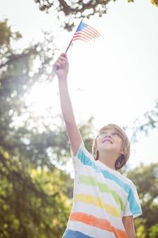 Jonge jongen die een amerikaanse vlag houdt