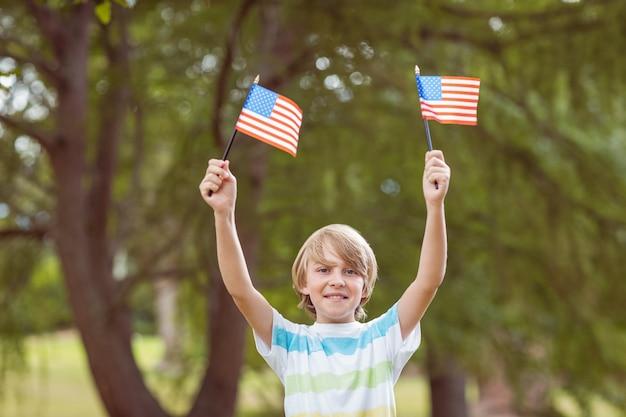 Jonge jongen die een amerikaanse vlag op een zonnige dag houdt